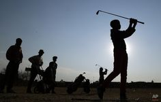 Ten-year-old boy Amohela Mokoena, right, watches his shot during a game of golf at a park in Katlehong township, east of Johannesburg, South Africa, Thursday, July 16, 2015. (AP Photo/Themba Hadebe)