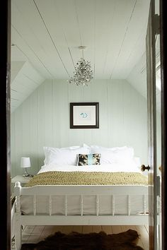white bedding/wood plank ceiling and walls