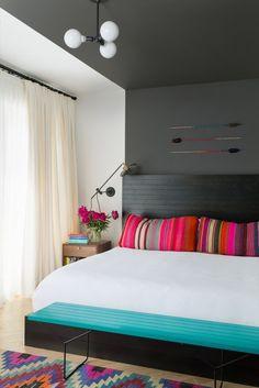 O quarto principal foi pintado de duas cores,  branco e cinza, que se alinha com a cabeceira da cama, une-se ao teto e para baixo na parede oposta.