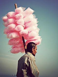 Beautiful photo of a man selling cotton candy.  Love the contrast of the heavy textures in his face, almost like carved wood, against the innocent airy nature of the cotton candy.  Perfect.