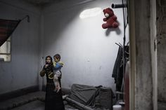 Syrian Arab Republic, 2012 - A woman and her child stand inside their house after it was damaged by bombing, in a city affected by the conflict. The light on the top centre of the wall behind them comes through a hole caused by a mortar shell. - © UNICEF/NYHQ2012-0213/Alessio Romenzi - http://www.unicef.org/photography