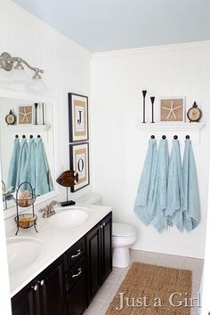 "Love this coastal bathroom decor! Wonderful white walls and countertop, contrasted with the ebony cabinets and accented with the neutrals and that fabulous sea blue! This is my bathroom - even has my name ""Jo!"""