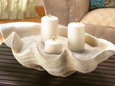 """fill a large """"faux"""" clam shell with pretty sand, grab a few pillars and voila you have an elegant centerpiece!"""