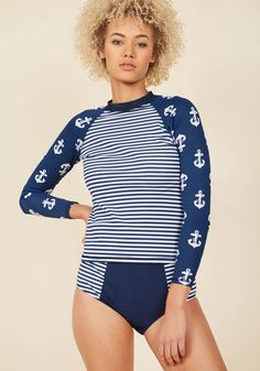 <p>Looking perfectly poised atop your board in this navy-striped rash guard, you instruct your pupils on proper technique in attention-grabbing style. A ModCloth exclusive by Girlhowdy, this top's raglan sleeves and anchor print captivate the class while keeping your look effortlessly afloat!</p>