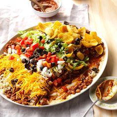 Texas Taco Dip Platter Recipe -When I'm entertaining, this colorful dish is my top menu choice. My friends can't resist the hearty appetizer topped with cheese, lettuce, tomatoes and olives. —Kathy Young, Weatherford, Texas