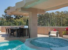 The backyard also features a barbecue station with a wet bar and multiple lounge areas.