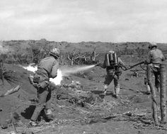 A US Marine uses a flamethrower against a Japanese pillbox as he is covered by two riflemen, Iwo Jima, February, 1945.