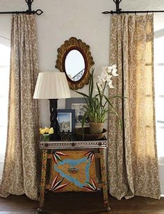Gorgeous patterned gold drapery, beautiful vignette between windows