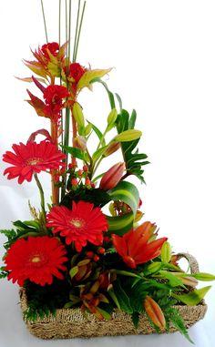 3 Gerberas, varas de Lilis al mismo color, follaje. Base en cesta de mimbre.