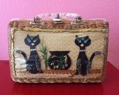 Vintage 1950s novelty wicker handbag featuring two black cats watching over a fishbowl. Classic mid-century kitsch piece! Made of hand-woven wicker and white pearly lucite handles and hardware. Lined with a burnt orange/brown pleather. One large pocket and one metal zipper pocket. Good condition. Small breaks to the outer plastic where spiky shells have poked through. Small breaks at the interior plastic where brackets attach. Wicker in excellent shape. Normal patina to hardware. Priced ...