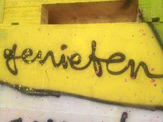 genieten. Dit is met graffiti op een muur geschreven.