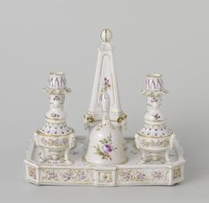 Porcelain Ink stand set consisting of a rectangular plateau on which stand an obelisk, two candlesticks, an inkwell, a sander and a handbell. All parts are decorated with multicolored bouquets and scattered flowers. Porseleinfabriek Den Haag (possibly), c. 1777 - c. 1790 - Dim: h 25 cm × w 27.6 cm