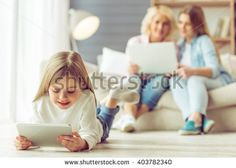Little girl is using a tablet, in the background her mom and granny are using a laptop while sitting on sofa at home - stock photo