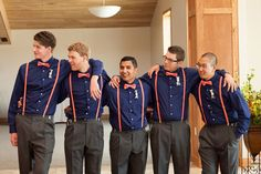 Groomsmen in navy button-up shirts, coral suspenders, and coral bow ties for nautical wedding.