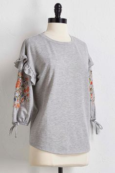 This popover top brings casual to a whole new level with ruffled tie sleeve detail and colorful floral embroidery. 3/4 sleeves.  65% polyester, 35% cotton Machine wash Imported