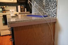 He installed the granite tiles on the old pink countertops with the help of cement board in between.  He then used a grinder to smooth the edges of the corners to make them round.  Here is what the layering looked like: