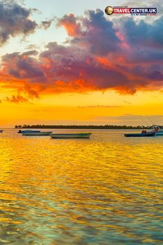 A panoramic view of fishing boats amidst the sunset backdrop in Le Morn Brabant, Mauritius features the charming skyline and lagoon. Sunsets are always heart-touching. #mauritius #sunset #twilight #boats #itsallabouttravel #travelcenteruk