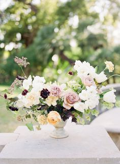 Spring colour palette in buttery yellows soft mauve and lilac with whites and burgundy/black centerpiece