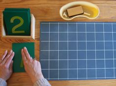 Now that the child has experienced the quantity/the concrete (Number Rods or Spindle Boxes or counting objects... from one to five), and has been given the abstract symbol (numbers one to five...) she may want to write the one and the zero. Use a squared chalkboard and sandpaper numbers. Trace with two fingers from top to bottom. Say