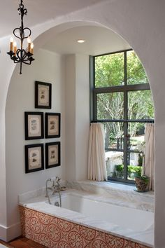 Elegant Bathtub Surrounds look Other Metro Mediterranean Bathroom Inspiration with arched wall opening cafe curtains chandelier Framed Artwork marble tub deck metal window telephone