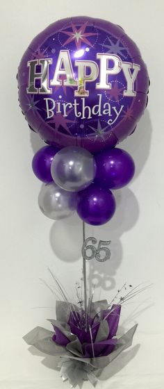 Purple and silver happy birthday balloon table decoration. 65th birthday.