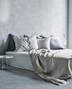 En stor seng tæt ved gulvet redt op med lysegrå tekstiler.