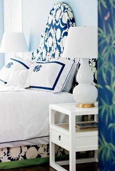 beautiful blue and white room. monogrammed pillows, printed fabric headboard, and white accents.