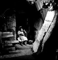 01-1951 Niña come en la puerta de su vivienda