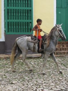 young boy on a horse in trinidad, cuba rides through the cobblestoned streets