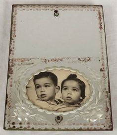 Mirror containing photos of Paul and Tereza Vadasz's two children, Robi and Guri, aged five and three, who were deported together with their parents from Oradea Mare, Hungary to Auschwitz and murdered there. The father, the sole survivor, returned to his home where he found the mirror.