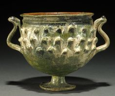 Roman green lead-glazed chalice, 1st-2nd century A.D. With three rows of applied pinecone scales and twin ribbed handles, interior glazed honey-brown, some silvery iridescence, 8.9 cm high. Private collection