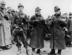 """Hitler Youth boys pressed into army service enjoy a bite after becoming POWs near Berstadt, Hesse. They and the smiling adults around them were captured by the 3rd US Army, April 1945. The boys would surrender their uniforms, put on civilian clothes and then become """"displaced persons"""" under the guide of the Red Cross."""