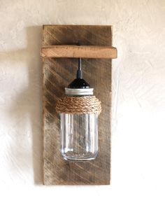 """This mason jar light fixture is the perfect wall sconce for rustic, country, or western décor. Made from reclaimed barn wood, it looks great with or without the rope detail. Hang one on either side of the bed or bring a rustic touch to your living room.  ROPE ACCENT OPTIONAL This sconce is available with or without the rope accent. Please select which variation you want when purchasing.  SIZE The finished product is 7.25"""" wide x 16.5"""" high x 6.5"""" deep.  LIGHT BULB & INSTALLATION This fixture…"""