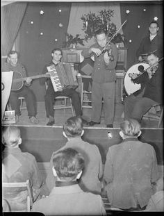 Prisoner of war concert, 1945    German prisoners of war listen to a concert put on by some of their fellow POWs at a prisoner of war camp in Britain. The decorations around the stage and piano indicate that it may be Christmas-time.