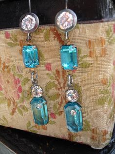 Aqua Aqua Awesome Earrings From matte finished silver plating over brass with a beautiful round CZ ear wires hangs 2 vintage components. The top connector is faceted aqua class in an amazing clear color. From that hangs a very unique vintage drop. The top is a round clear glass rhinestone and attached at the bottom is a cushioned rectangular stone in aqua with flashes of gold and green. Embedded in that aqua stone is a tiny clear rhinestone! This was a very special find...