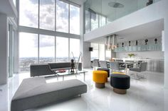 Kevin Gray designed this spectacular, triplex penthouse in downtown Miami. White glass floors laid on the diagonal reflect the city skyline. Collectible furnishings from Gabriella Crespi, and charcoal gray upholstered sofas complement the clients' evolving modern art collection. Glass and steel floating staircase provides access to the second level bedrooms, enclosed by glass partitions and draperies. Upper floor includes a private pool deck and stunning views of Biscayne Bay.