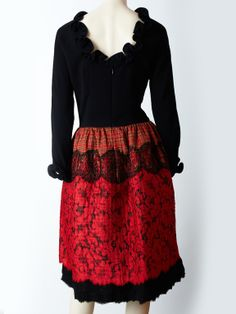 Geoffrey Beene, red and black whimsical cocktail dress. Dress has a fitted jersey bodice that ends at the hip with an open back and a ruffle neckline and cuff. Skirt starts at the hip, is quilted and is a made of a patchwork of fabrics which includes a red and black lace overlay on top of red tartan - like plaid.