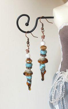 Boucles d'oreilles bohèmes et tribales composées de ! - une magnifique breloque en verre filé, une perle au chalumeau artisanale, de 1 cm de large (au plus large) et 3.2 cm de long (au plus long). Elle est de couleur marron translucide, turquoise et blanche, magnifiquement fixée sur une tige en cuivre. - un palet de coco couleur turquoise, une perle de bohème à facettes et incrustée de reflets, et enfin une perle en nacre véritable. 7.5 cm de long.