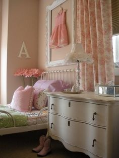 Lovely feminine bedroom. Love the frame around the little pink dress.