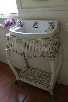 .Old sink in vintage wicker table.  Love it!