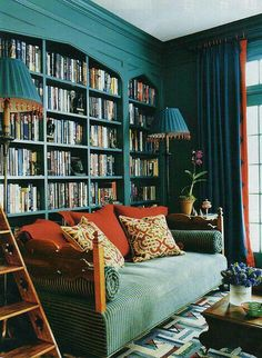 Dark teal and orange-red pillows. Could read in this room for a long time.