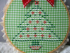 Christmas Tree Hoop Art. Christmas Tree is made using the hand embroidery chicken scratch stitch, stitched on green and white gingham fabric. Floss colors are white, red and green, mounthed in a wood embroidery hoop with white lace trim and has a cute red bow attached at the top. Measures 8 inches including the lace trim. more Christmas tree hoop art.. https://www.etsy.com/listing/170361888/christmas-tree-embroidery-hoop-art-hand