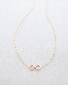 Tiny Handmade Infinity Necklace in gold, silver and rose gold by Olive Yew. This tiny infinity charm necklace is handmade and hand hammered for durability.