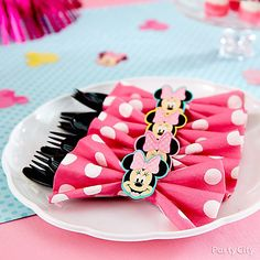 She'll love a Minnie-themed first birthday filled with DIY touches! To whip up these clever pink bow cutlery packs, wrap up black utensils in a napkin creased to look like a bow. Tie with a small piece of ribbon, and cover with a sweet Minnie cutout. Click for more adorable Minnie Mouse first birthday tips!