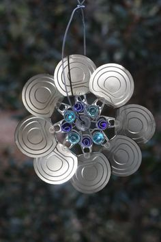 Soup can lids become wind spinners and sun catcher for inside, porch, or yard……