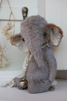 kit for 5.5 inch elephant designed by Olga Orel for Noble Fabrics, the kit includes hand dyed grey viscose, fabric for inner ears, joints, green glass eyes, small piece of oil chalk for ageing and some black thread for aged stitches, strong thread, rusty bell & pom po ribbon slight aged