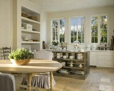 what a view out those windows! Love the stucco shelves and island in grey with the light natural wood dining table.