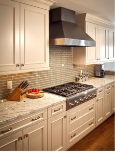like the white cabinets and granite color but with dark wood floor and white vent hood here is an example of white kitchen with grey glass subway tile