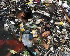2 kinderen in de Yamunarivier in India, wordt gebruikt voor afval en als was- en drinkwater.