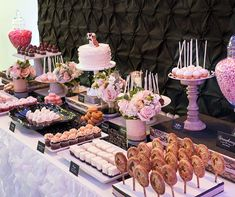 A dessert table of lollipops, cupcakes and jars of strawberry jelly beans are arranged in a colorful display. #buffet